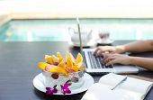 stock photo of fruit bowl  - Business people working at home on laptop computer with bowls of fresh fruit by swimming pool - JPG