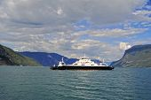Ferry is seen sailing across fjord in Norway on a sunny summer day