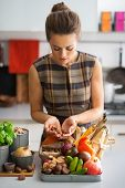 Young Housewife With Vegetables In Kitchen