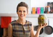 Portrait Of Happy Young Housewife Showing Jar Of Pickled Cucumbe