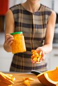 Closeup On Young Housewife Showing Jar Of Pickled Pumpkin And Pu