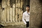 Handsome young man between ancient marble columns