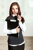 Secretary Holds A Black Folder On Your Chest And Held A Pen To Her Mouth