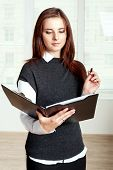 Girl Holds A Black Folder Open In One Hand And In The Other She Holds A Pen