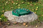 picture of manhole  - image of one Green Manhole in park at day - JPG