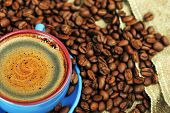 stock photo of coffee crop  - Cup of coffee and spilled out coffee beans - JPG