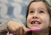 Girl Without A Tooth While Brushing Teeth In The Bathroom