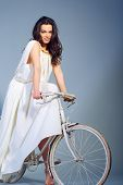 Young woman in dress riding a bicycle