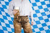 Bavarian man with leather pants (Lederhose) holds Oktoberfest beer stein (Mass).