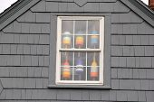 pic of upstairs  - Colorful nautical buoys hanging in upstairs window of clapboard home by the seashore - JPG