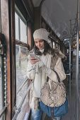picture of tram  - Beautiful young woman wearing ecological fur while texting on a tram - JPG