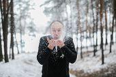 Groom Blowing Snow Off His Hands