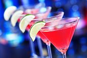 stock photo of cosmopolitan  - four cosmopolitan cocktails on the bar in front of blurred background. A cosmopolitan or cosmo is a cocktail made with vodka, triple sec, cranberry juice and freshly squeezed lime juice or sweetened lime juice. 