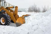 picture of bulldozer  - A bulldozer clears snow drifts after the storm - JPG