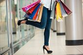 image of woman legs  - Woman legs with shopping bags against the backdrop of a shopping center - JPG