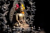 stock photo of pooja  - Buddha statue with yellow and red flowers in Patan Nepal - JPG