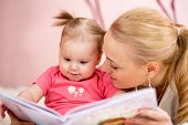 stock photo of nurture  - happy mother read a book to baby girl indoors - JPG