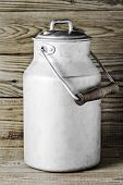 Aluminum old milk can on a wooden background in the vertical format