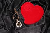 Heart-shaped jewelry casket with pendant placed on a black silk