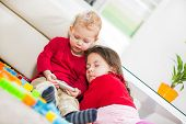 Two children playing on the carpet. Boyholding phone. Selective focus