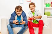 Happy friends hold joysticks and play game console