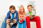 Happy teens hold joysticks and play game console