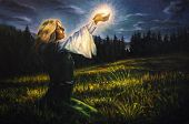 stock photo of canvas  - beautiful painting oil on canvas of a mystical young woman in green emerald medieval dress is holding a glowing ball of light in her palms amids a nocturnal meadow - JPG