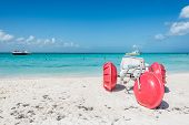 foto of tricycle  - Red giant Tricycle and people swimming at Caribbean Island - JPG