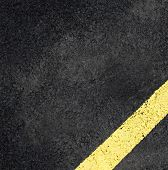 grungy, dirty view of asphalt with distinct yellow stripe