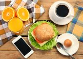 breakfast and moile phone on wooden table