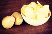 Potatoe chips in a bowl and potatoes. On wodden table.