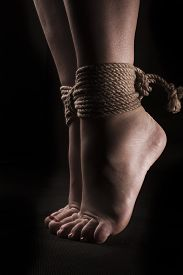picture of suspenders  - detail suspended bound feet submissive young girl on a black background  - JPG