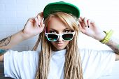 stock photo of dreadlock  - Modern teenage girl with blonde dreadlocks standing by the brick wall - JPG