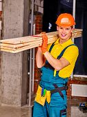 picture of millwright  - Happy man in builder uniform carry boards indoor - JPG