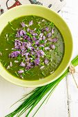 pic of edible  - Swiss chard and potato cream soup with chopped chives with edible chives flowers in green ceramic bowl - JPG