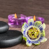 picture of zen  - beautiful spa concept of passiflora flower black zen stones and candles on wooden background closeup  - JPG