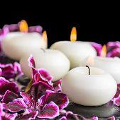 stock photo of geranium  - beautiful spa still life of blooming dark purple geranium flower beads and candles in reflection water closeup  - JPG