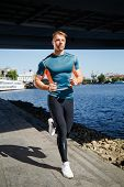 stock photo of leggins  - Young handsome man running along the embankment near the river under the bridge - JPG