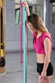 stock photo of pole dancing  - Young tired girl after pole dance training - JPG