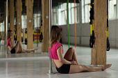 pic of pole dancer  - Pole dancer sitting on the floor and resting after training - JPG