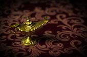 pic of aladdin  - Macro image of a tiny gold antique Aladdin lamp ornament close - JPG
