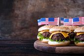 pic of burger  - Mini beef burgers with American flag on wooden backgoundselective focus and blank space - JPG