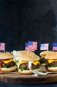 pic of beef-burger  - Mini beef burgers with American flag on wooden boardselective focus and blank space - JPG