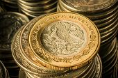 picture of golden coin  - A golden coin with an eagle over stacks of silver coins business wealth and success concept - JPG
