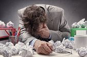 Постер, плакат: Overworked depressed and exhausted businessman at his desk with a pile of work or concept for frust