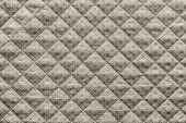 stock photo of quilt  - grained texture of beige quilted fabric with an abstract pattern from crosses - JPG
