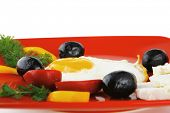 pic of scrambled eggs  - fried scrambled eggs eye with white goat feta cheese on red plate isolated over white background with black olives and vegetables - JPG