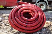 image of coil  - Red colored plastic tube coils on construction site - JPG