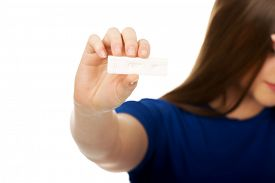 foto of teen pregnancy  - Unhappy teenage woman holding pregnancy test - JPG