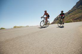 image of triathlon  - Athletes competing in the cycling leg of triathlon - JPG